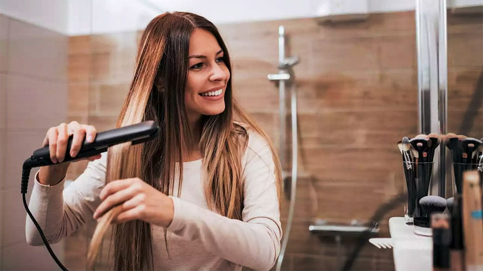 Frau glättet Haare mit Glätteisen
