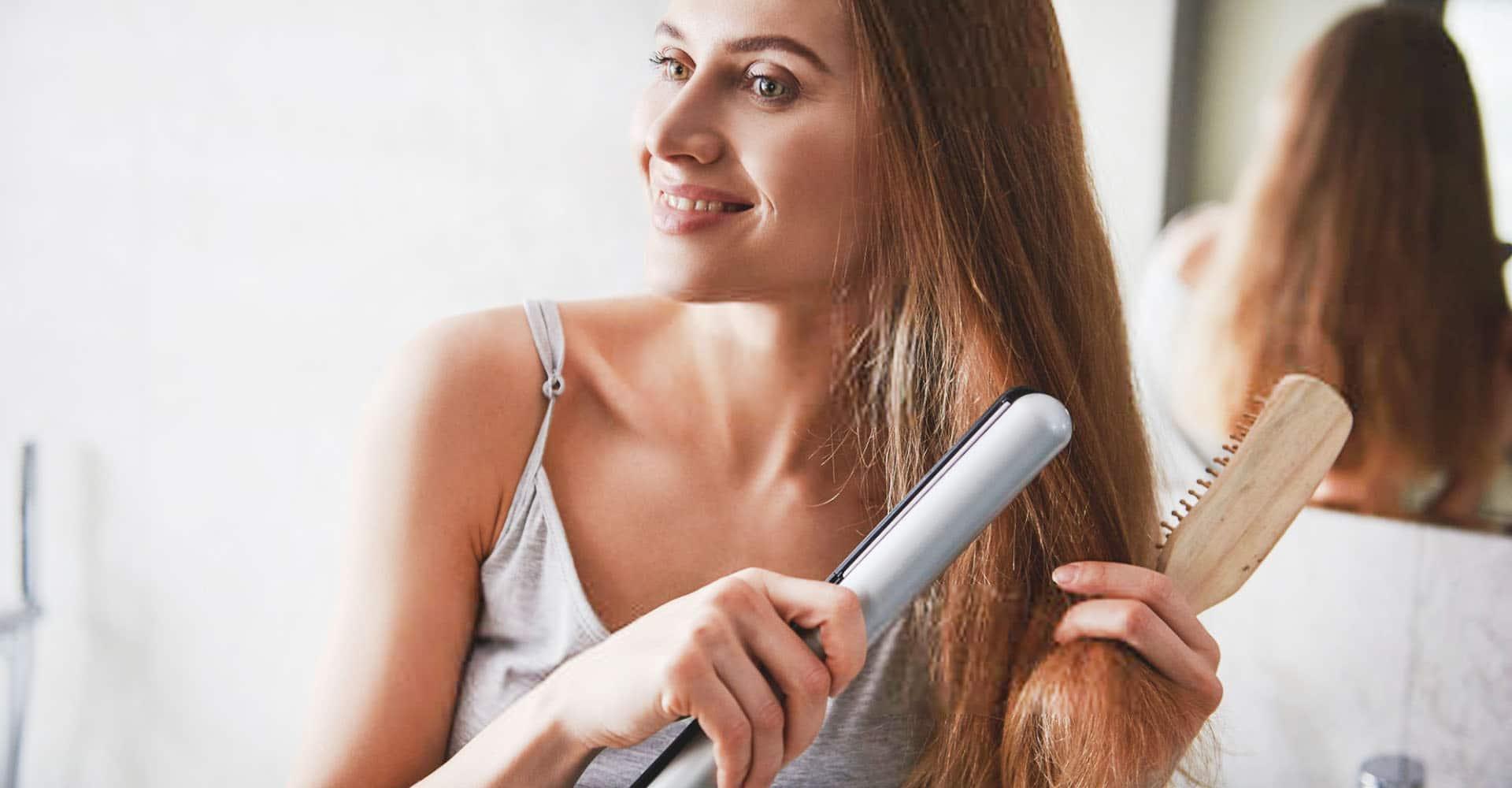 Frau glättet Haare im Haarglätter im Badezimmer vor Spiegel
