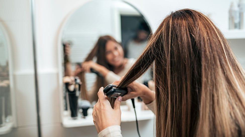 Frau macht Locken mit Lockenstab am Spiegel
