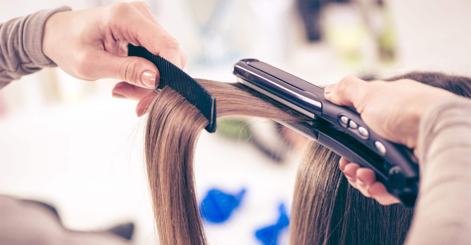 Frau werden Haare mit Glätteisen geglättet