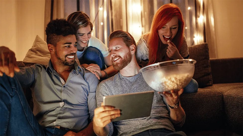 Freunde bei Filmabend mit Popcorn und Tablet
