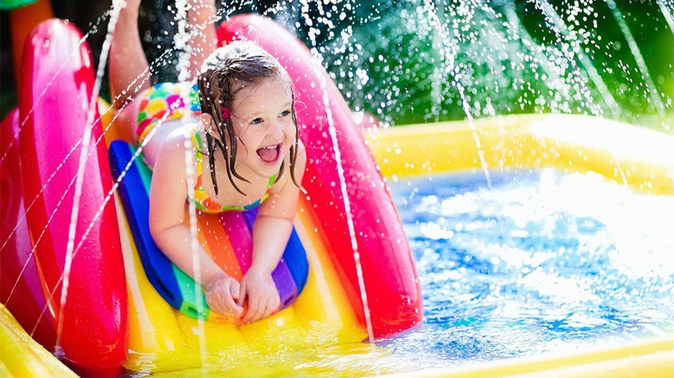 Mädchen in aufblasbarem Pool mit Rutsche