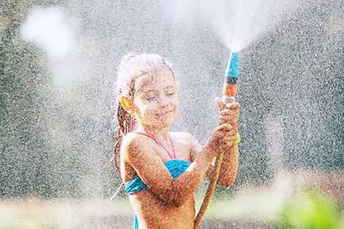 Mädchen kühlt sich im Sommer im Garten mit Wasserschlauch ab
