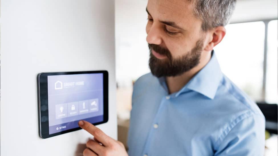 Mann bedient Tablet an Wand für Smart Home System