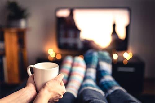Paar bei Filmabend mit Wollsocken und Tasse Tee vor Fernseher