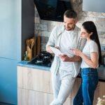 Paar nutzt Smart Home System in Küche mit Tablet