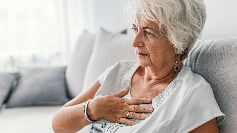 Ältere Frau mit Herzrasen hält sich Brust