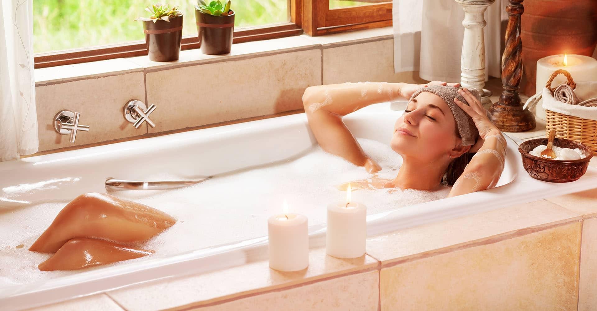 Frau entspannt auf Whirlpoolmatte in Badewanne