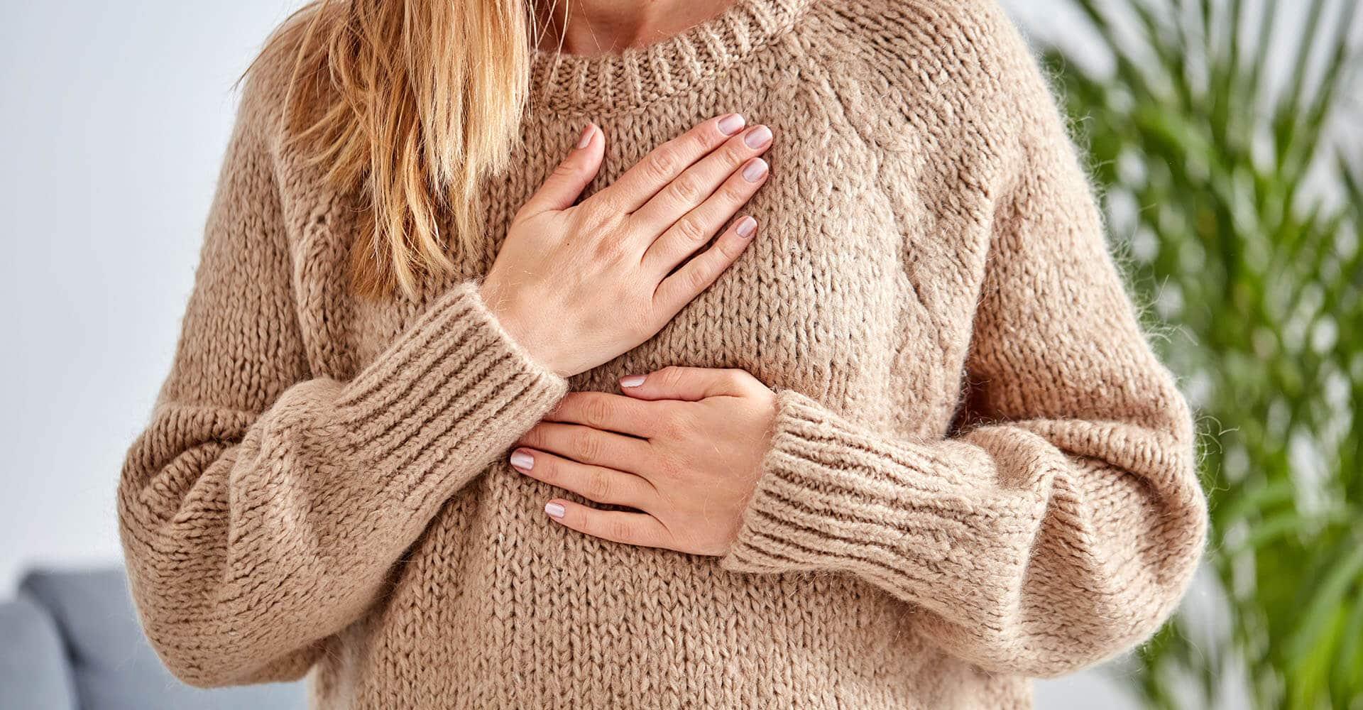 Frau mit Herzrasen hält sich Brust