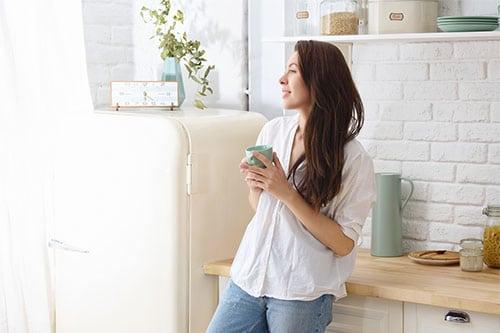 Frau mit Morgenroutine trinkt Kaffee