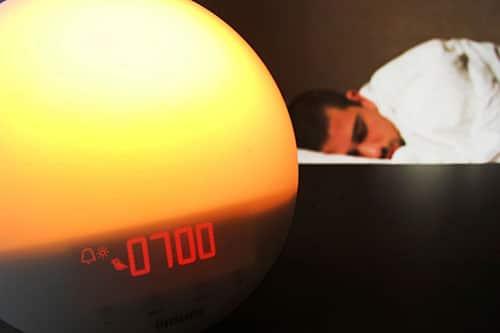 Mann schläft neben Lichtwecker