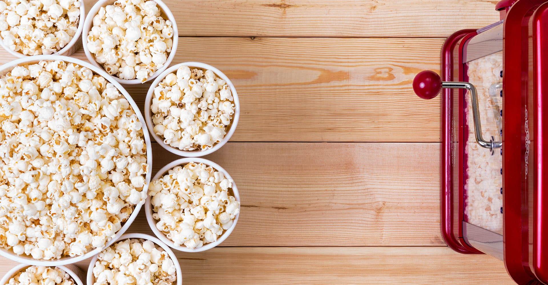 Popcornmaschine vor Kino-Eimern mit Popcorn
