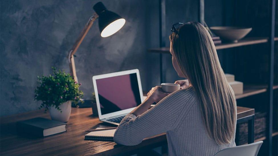 Frau arbeitet mit Schreibtischlampe an Bürotisch