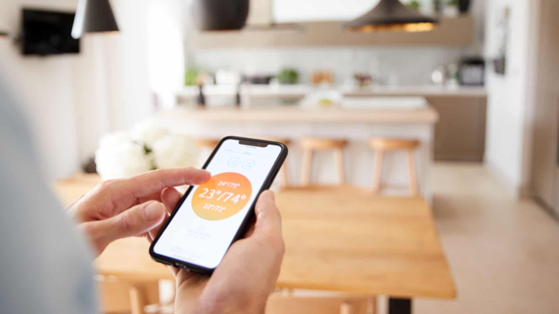Frau mit Smartphone an Smart Home Heizung