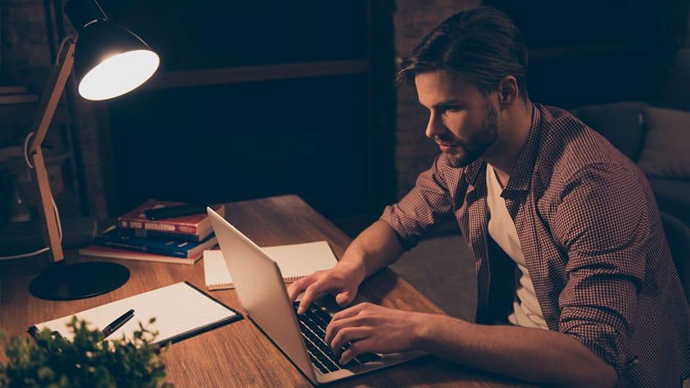Mann arbeitet mit Schreibtischlampe