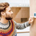 Mann justiert Smart Home Heizung