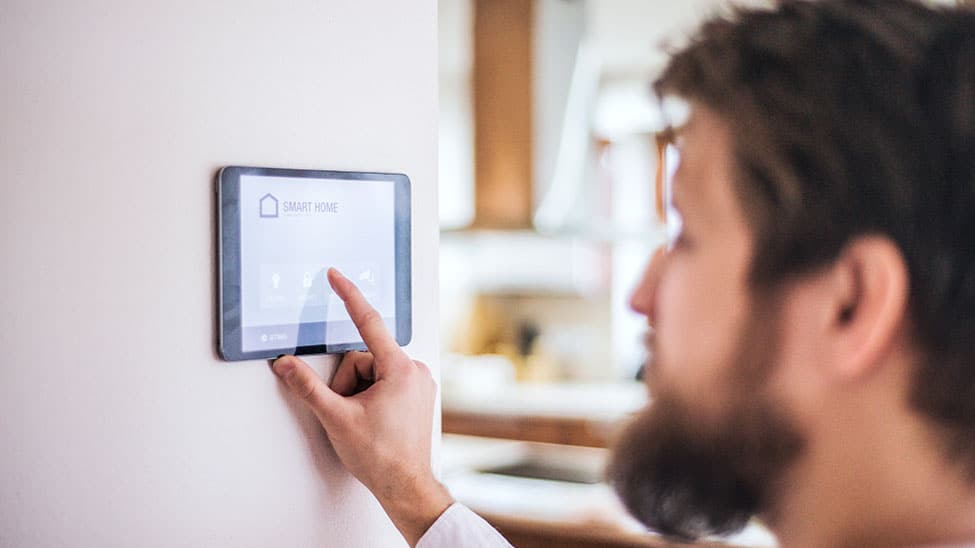 Mann regelt Temperatur via Smart Home Heizung
