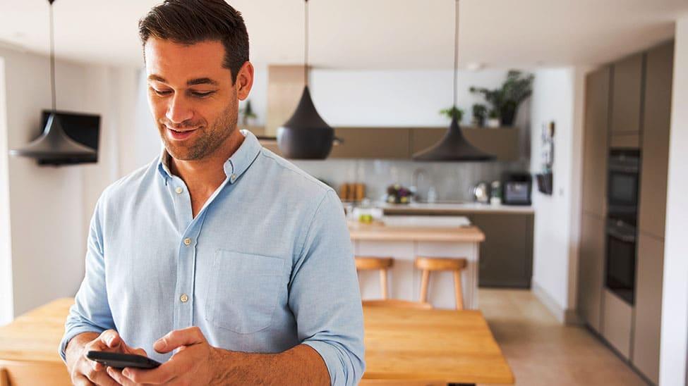 Mann steuert Smart Home Heizung mit Handy