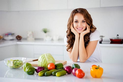 Abnehmen ohne Diät - Frau in Küche mit Gemüse
