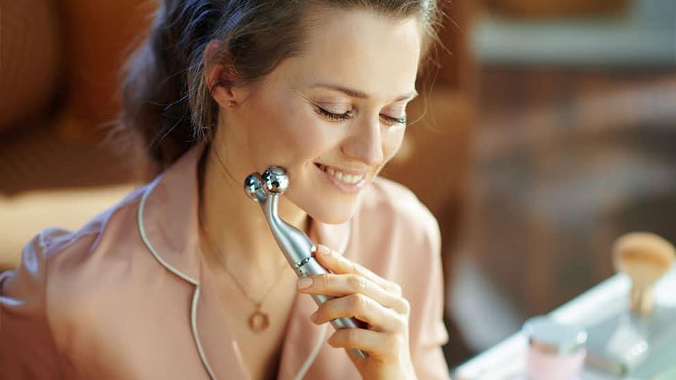 Frau nutzt Handmassagegerät