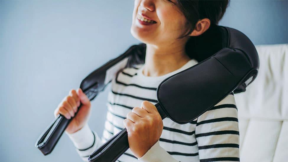 Frau nutzt Rückenmassagegerät