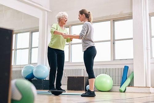 Alte Frau trainiert mit Balanceboard