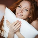 Frau mit Dinkelkissen im Bett