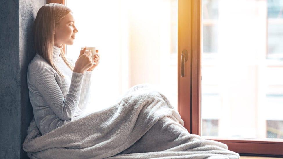 Frau mit Heizdecke schaut aus Fenster