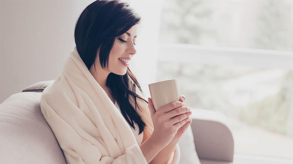 Frau mit Heizdecke trinkt Tee