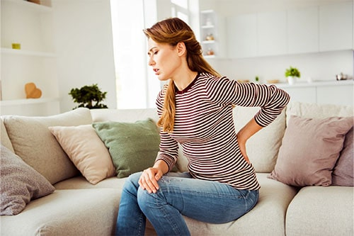 Frau mit Rückenschmerzen braucht Massagekissen