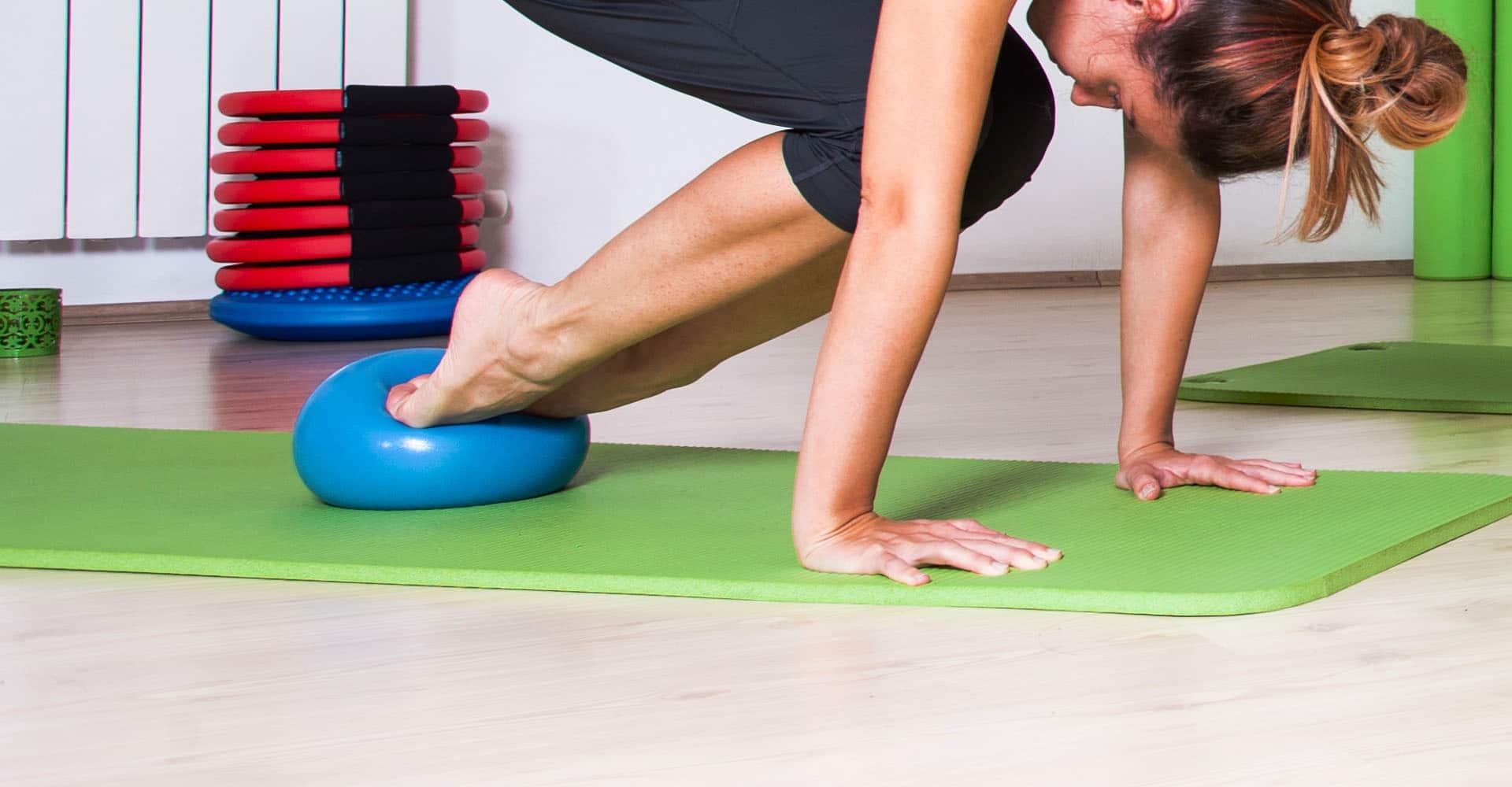 Frau trainiert mit Balancekissen