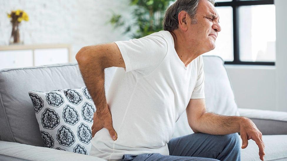Mann mit Rückenschmerzen braucht Massagekissen