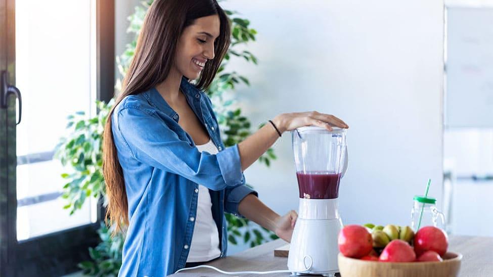 Frau bedient Smoothie Mixer in Küche