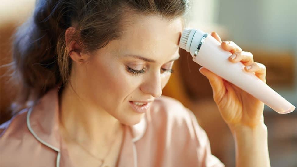 Frau mit Gesichtsreinigungsbürste an Stirn