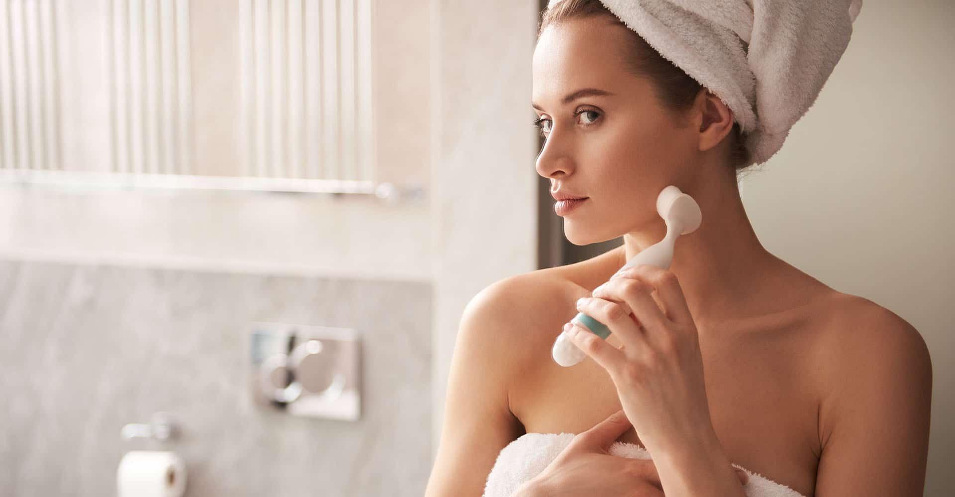 Frau mit Gesichtsreinigungsbürste in Bad