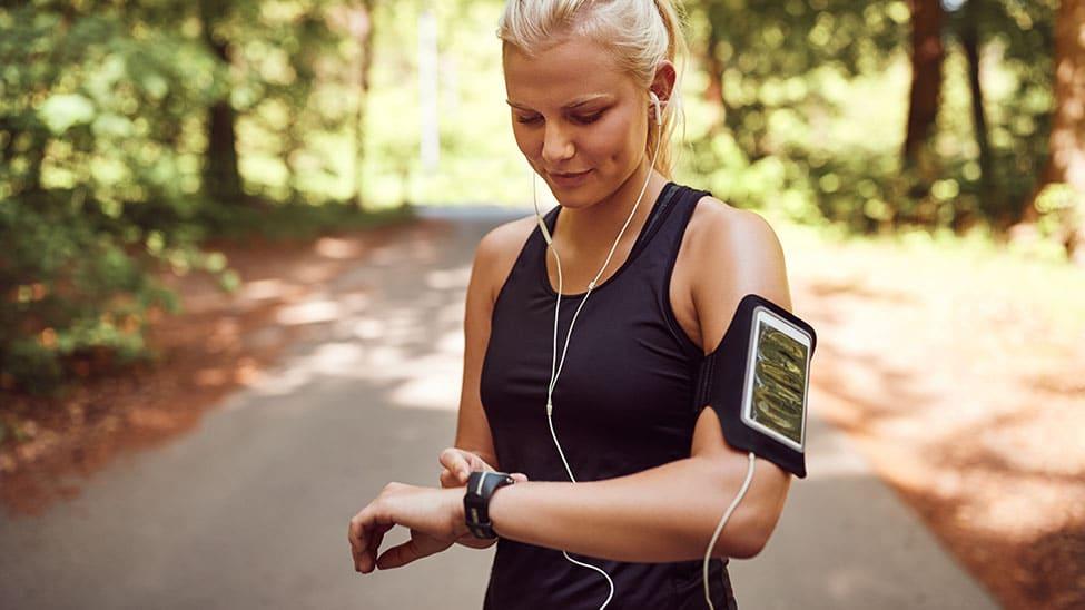 Frau nimmt Puls mit Herzfrequenzmesser beim Joggen