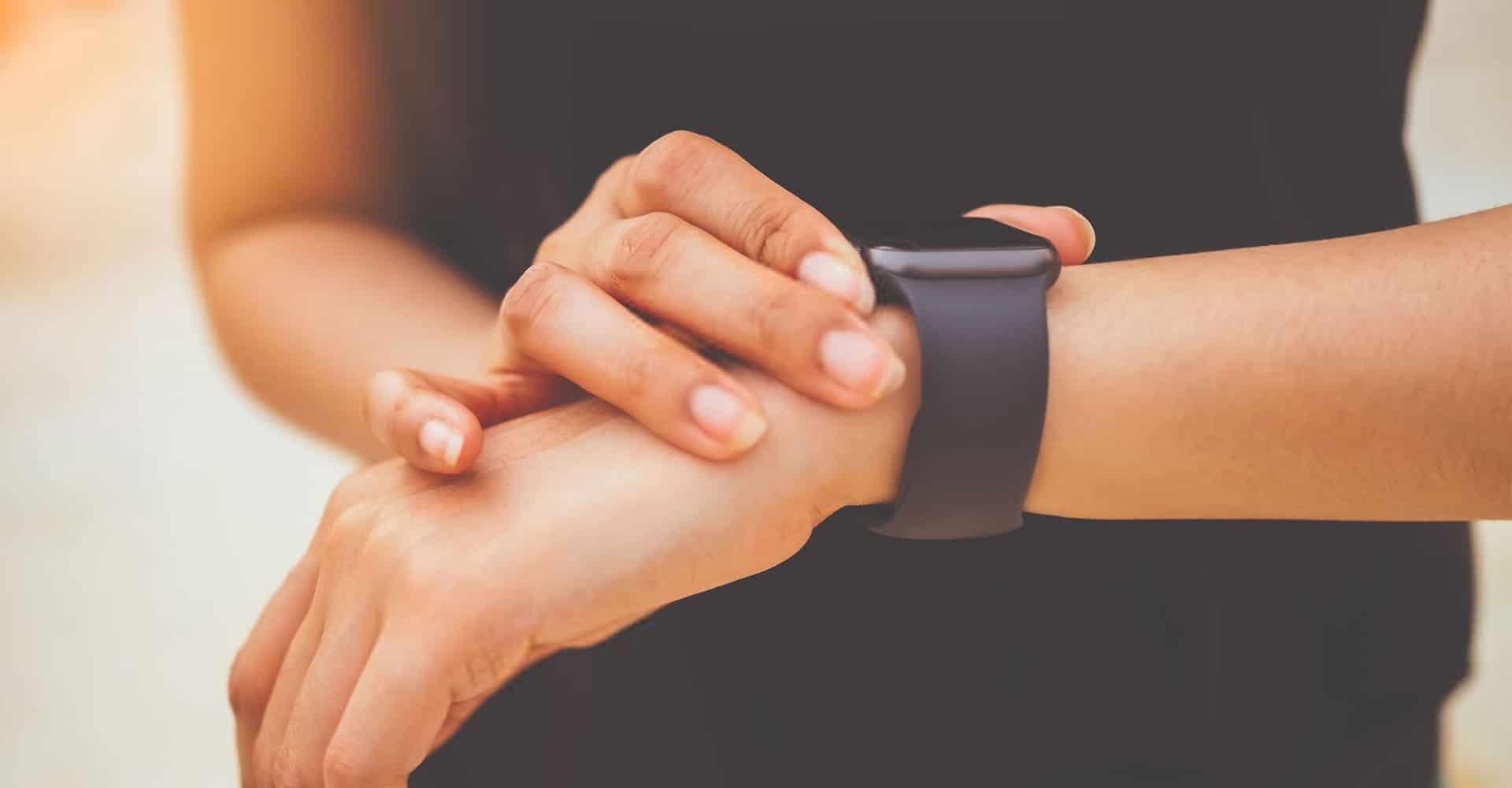 Frau nimmt Puls mit Herzfrequenzmesser