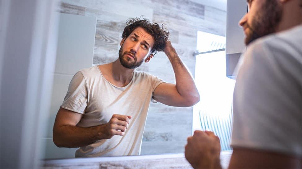 Mann mit Locken mit Haarwachs vor Spiegel