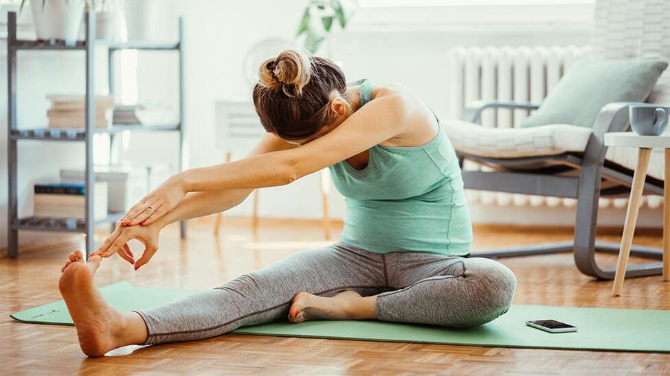 Frau dehnt sich mit Yogahose