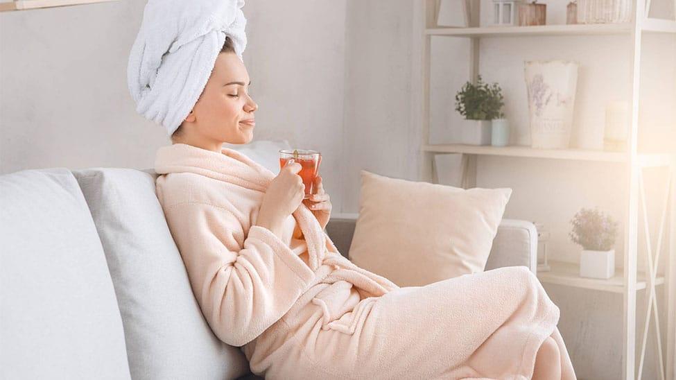 Frau in Bademantel auf Sofa zuhause