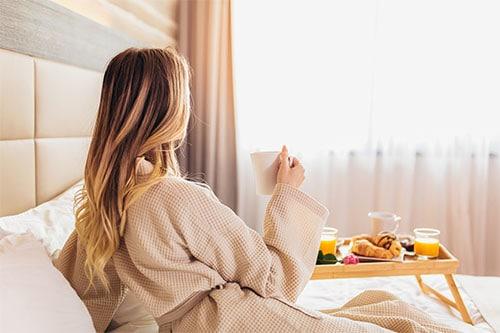 Frau in Bademantel und Frühstück im Bett