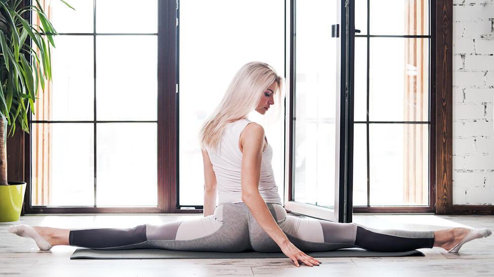 Frau macht Spagat mit Yogahose