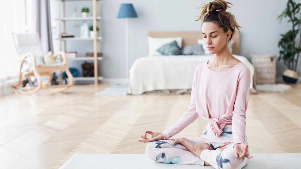 Frau macht Yoga mit Yogahose im Schlafzimmer