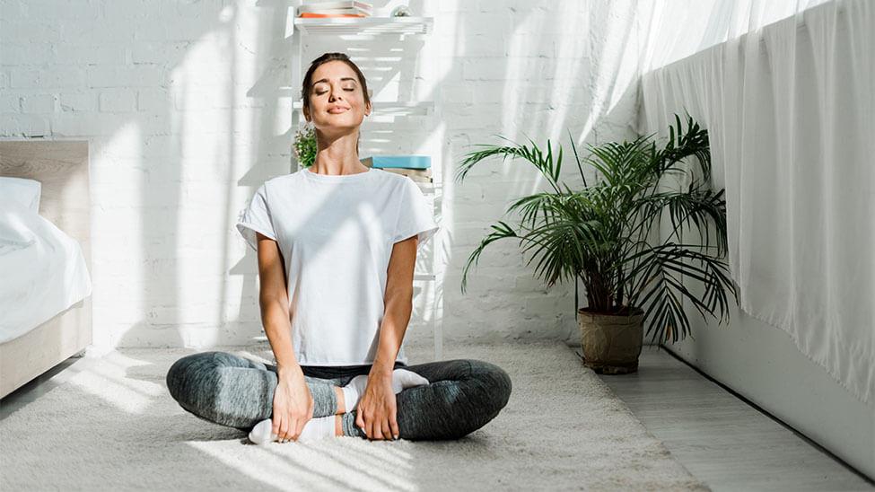 Frau meditiert mit Yogahose neben Bett