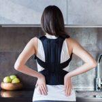 Frau mit Rückenbandage in Küche