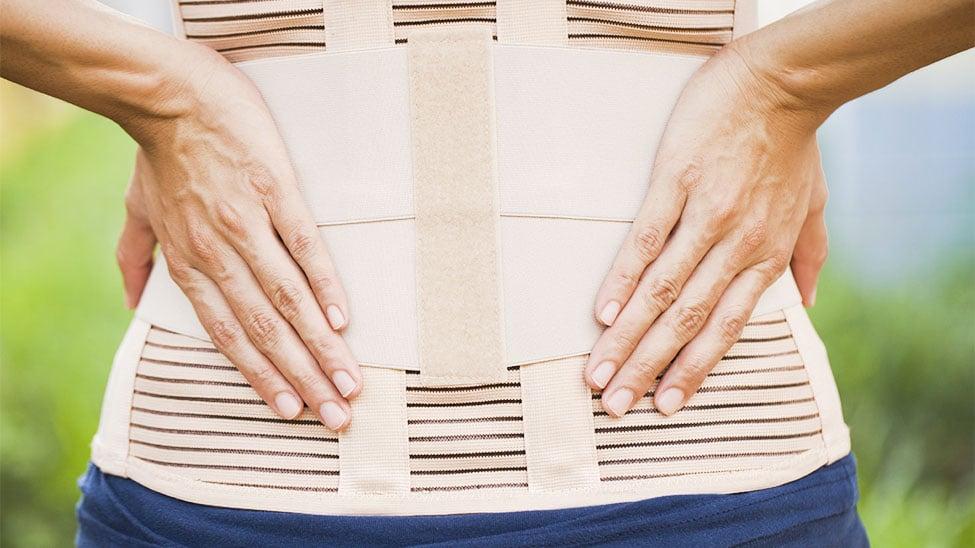 Frau mit Rückenbandage stützt Rücken