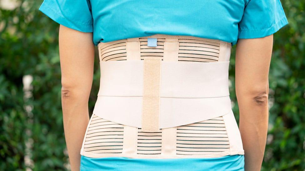 Frau mit Rückenbandage steht draußen