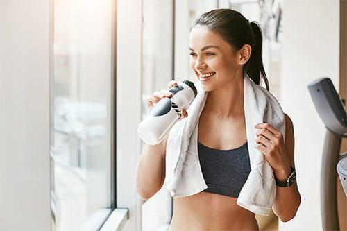 Frau mit Sport-Trinkflasche nach Training