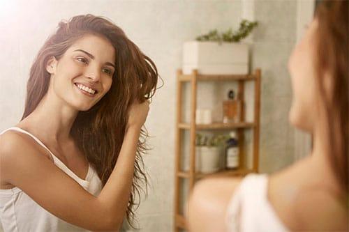 Frau nutzt Haarkur