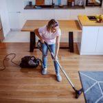 Frau nutzt Staubsauger mit Wischfunktion